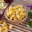 Uncooking pasta in bamboo bowl — Stock Photo