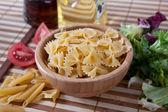 Uncooking italian pasta farfalle in bowl — Stock Photo