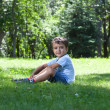 Stock Photo: Portrait of cute little boy sitting on the grass