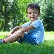 Portrait of cute little boy sitting on the grass — Stock Photo