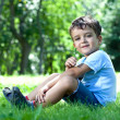 Portrait of a boy, sitting on green grass, smelling flower — Stock Photo