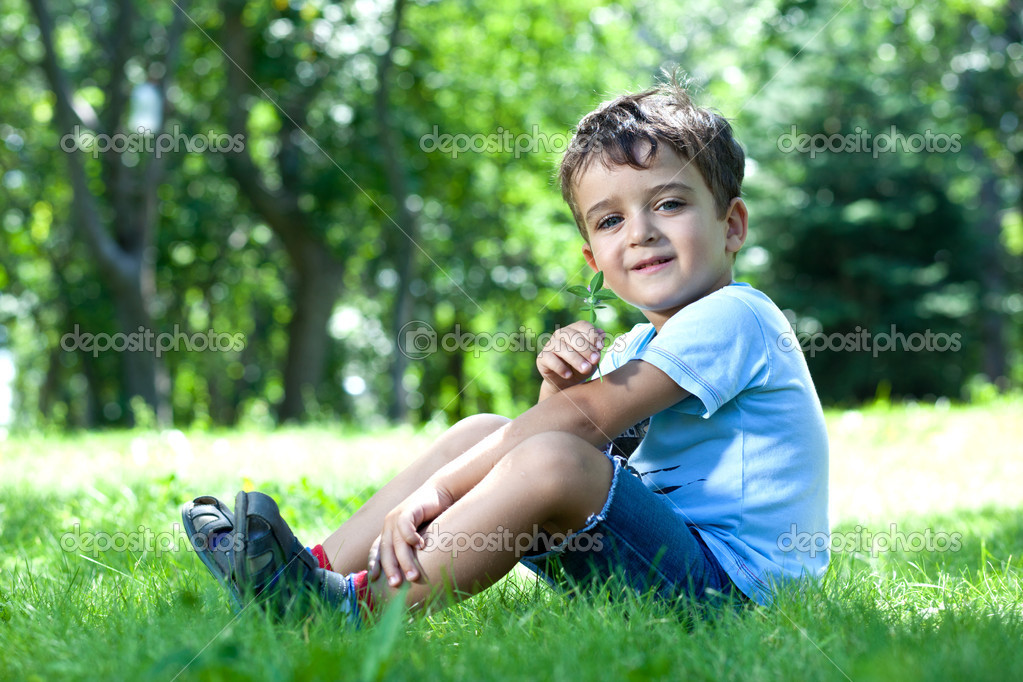 Portrait of a boy, sitting on green grass, smelling flower — Stock Photo #11545671