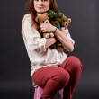 Girl with soft toys sitting on a chair — Stock Photo