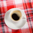 Cup of coffee on a red tablecloth — Stock Photo