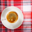 Cup of coffee on a red tablecloth — Stock Photo #10794105