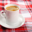 Stock Photo: Cup of coffee on a red tablecloth