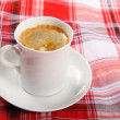 Cup of coffee on a red tablecloth — Stock Photo #10794114