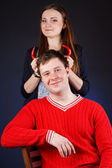 Beautiful girl with young man with red horns made of pepper — Stockfoto