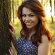 Portrait of young woman hugging a big tree in a park — Stock Photo #10829354