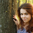 Portrait of young woman hugging a big tree in a park — Stock Photo #10829432