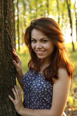 Portrait of young woman hugging a big tree in a park — Stock Photo
