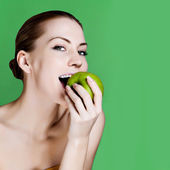 Woman eating apple smiling on green background. Healthy eating candid woman. — Stock Photo
