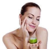 Happy smiling beautiful woman applying moisturizer cream on the face — Stock Photo