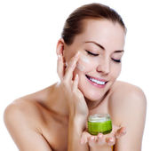 Happy smiling beautiful woman applying moisturizer cream on the face — Fotografia Stock
