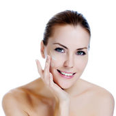 Happy smiling beautiful woman applying moisturizer cream on the face — Стоковое фото
