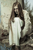 Zombie meisje zit in een verlaten gebouw — Stockfoto
