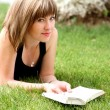 Young beautiful girl reading in the park — Stock fotografie