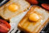 Fried eggs on black — Stock Photo
