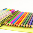 Color pen and pencils on the yellow writing-book — Stock Photo