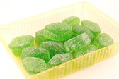 Green fruit jelly in yellow case — Stock Photo