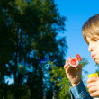 Little girl blowing soap bubbles — Stock Photo #10765924