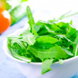 Green rucola fresh salad in white bowl — Stock Photo