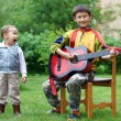 Two funny boys music student singing and playing the guitar outd - Stock Photo