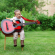 Stock Photo: Little music student singing and playing guitar outdoors