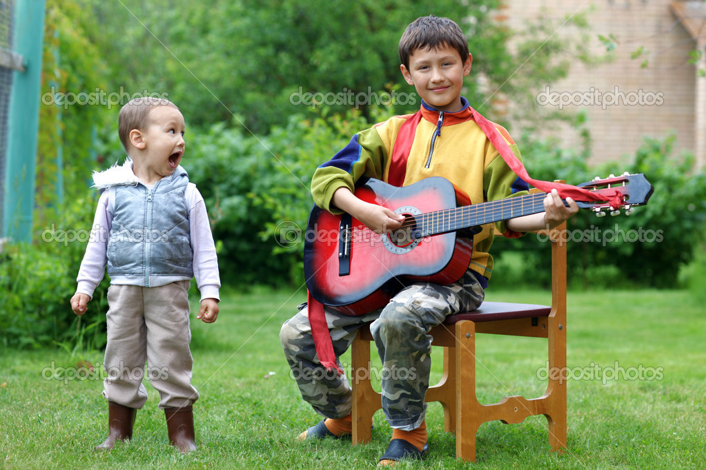 Two funny boys music student singing and playing the guitar outdoors — Zdjęcie stockowe #11052191
