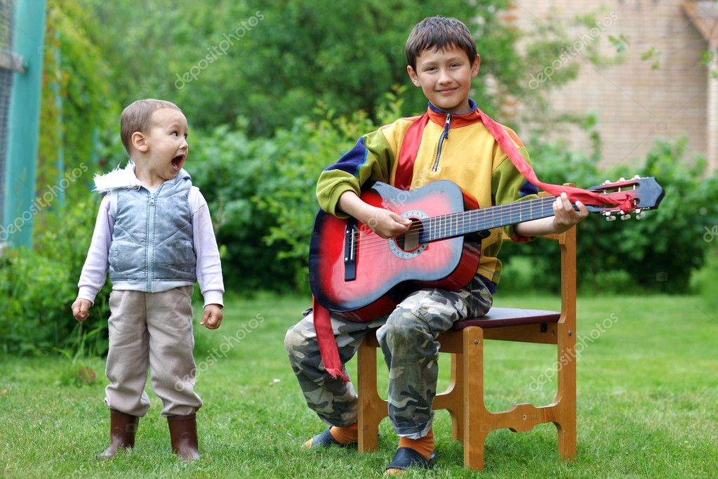 Two funny boys music student singing and playing the guitar outdoors — Foto Stock #11052191