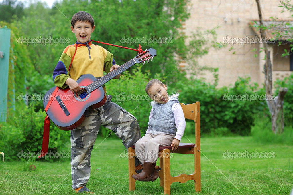 Two funny boys music student singing and playing the guitar outdoors  Stock Photo #11052236