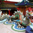 Old Dragon on oriental temple roof - Stock Photo