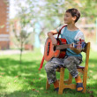 Music student playing the guitar outdoors — Stock Photo #12379833