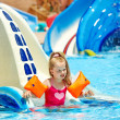 Child with armbands playing in swimming pool. - Stock Photo