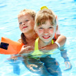 Child with armbands in swimming pool - Stock Photo
