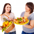 图库照片: Women choosing between fruit and hamburger.