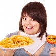 Overweight woman eating hamburger. — Stock Photo