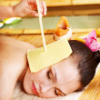 Stock Photo: Womgetting massage with ear candle .