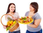 Kvinnor att välja mellan frukt och hamburgare. — Stockfoto