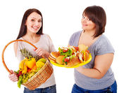 Women choosing between fruit and hamburger. — Stok fotoğraf
