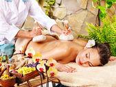 Woman getting thai herbal compress massage. — Stock Photo