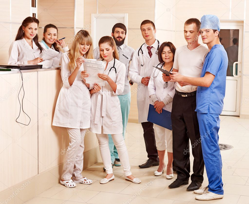 Group happy doctors standing at reception in hospital.  Stock Photo #11295049