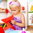 Child cutting out scissors paper in kindergarten — Stock Photo #11831848