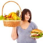 Woman choosing between fruit and hamburger. — Stock Photo #11832054