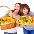 Women choosing between fruit and hamburger. — Stock Photo #11832066