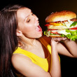 Woman bite hamburger. - Stock Photo