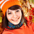 Stock Photo: Young woman in autumn orange leaves.