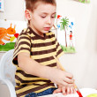 Child with picture and brush in play room. — Stock Photo #11833741