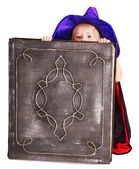 Witch little girl holding book. — Stock Photo