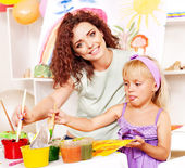 Child girl and teacher painting in school — Stock Photo
